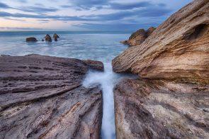 Landscape of rocks under Mount Maunganui at twilight