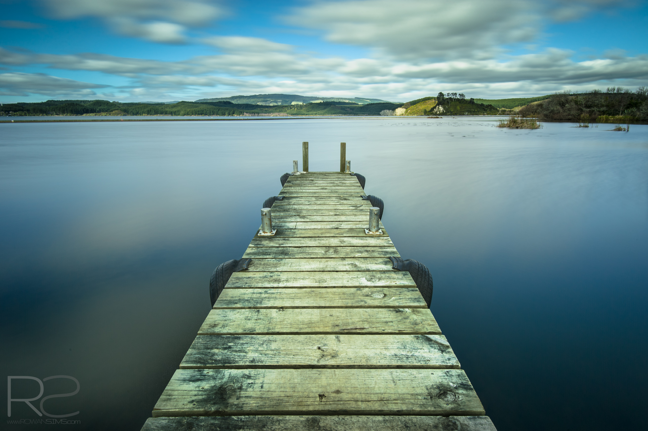 Long exposure landscape photo of a jetty in Waipuna Bay, Lake Rotoiti, Rotorua, New Zealand