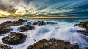 Waves crash over rocks under Mt Maunganui, New Zealand