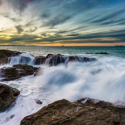 Waves crash over rocks under Mt Maunganui, New Zealand