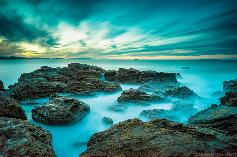 Long exposure landscape photo of rocks at sunset Mt Maunganui New Zealand