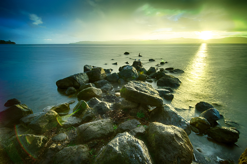 Landscape of sunset over rocks in Lake Taupo, New Zealand