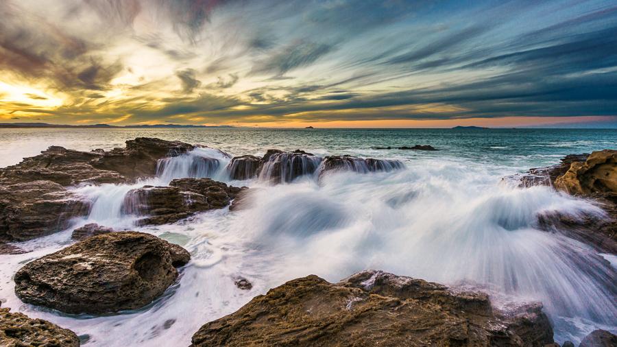 crashing waves on rocks in Mount Maunganui, New Zealand