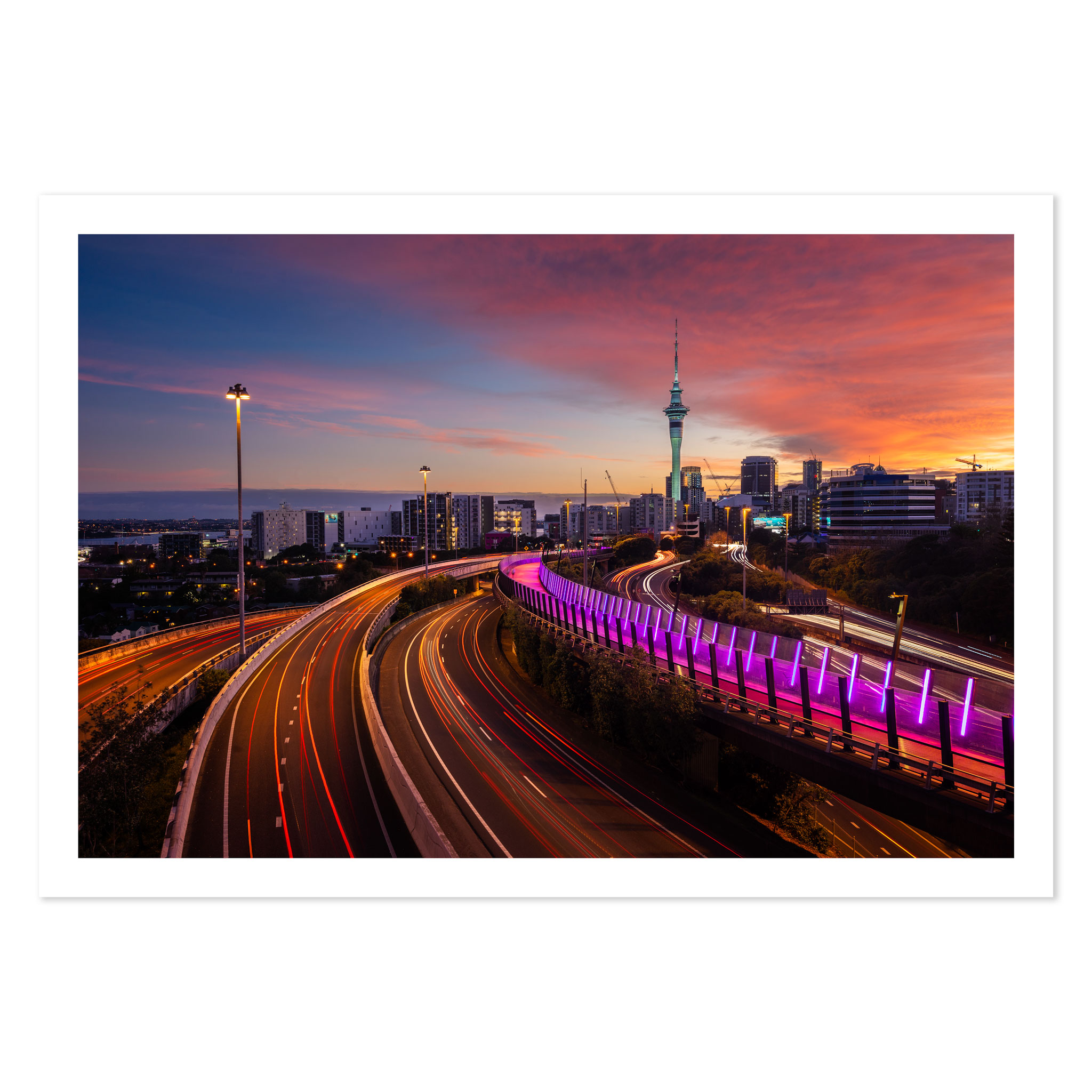 View of Auckland city skyline, Sky Tower, and motorway with car trails at sunrise.
